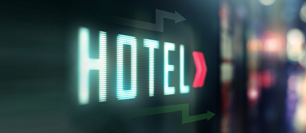 """A neon-lit sign reading """"hotel"""""""